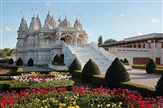 Ornate white temple, wide flight of steps to the front with lots of colourful flowers in the gardens