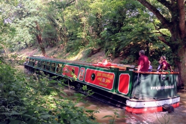 Large green and red barge boat on the canal in a wooded area
