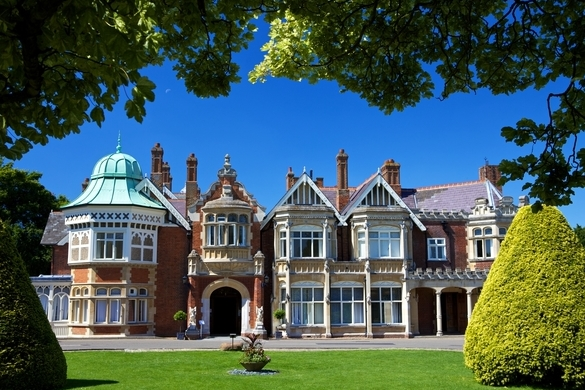 Bletchley Park mansion with copper green dome on the left of the roof, manicured lawn and trees