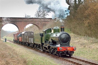 Steam train that has passed through a viaduct, green engine with red carriages and smoke billowing