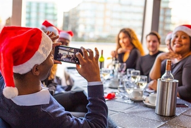 People sat at a table, wearing red santa hats, one taking a photo while they have a festive lunch