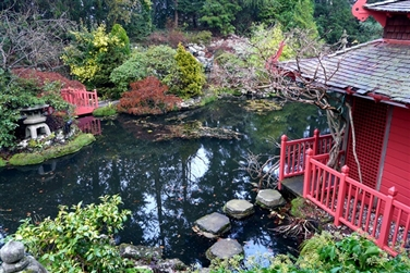 red bridge in a garden with a large pond, stepping stones and a red japanese style building