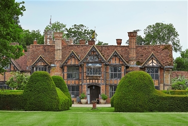 An image of Dorney Court exterior, showing a large Tudor manor house set in its landscaped garden