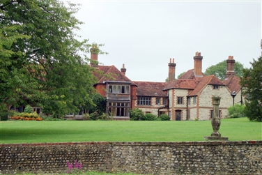 Back view of Manor House, tree to the left of the green lawn, garden ornament in front of stone wall
