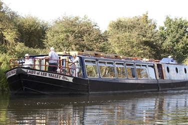 Image of Lady of Lee Valley Barge on the River Lee in Broxbourne with tranquil scenery beyond