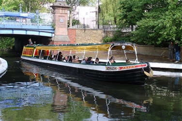 A long barge with a waterproof fabric roof, on the Regent's Canal with a bridge in the background
