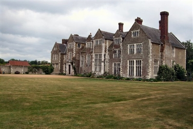 Historic Manor House with large chimney stacks with a lawn in front