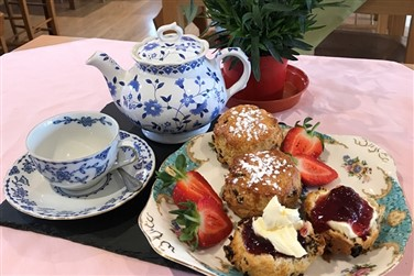 Cream tea served on crockery with tea pot and teacup