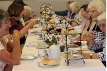 Visitors sat at a table enjoying afternoon tea served on stands