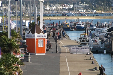 Visitors walking around Poole harbour with boats on the water and a ticket kiosk for boat trips