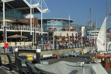 Gunwharf Quays building on the left with eateries' outdoor seating areas, boats in the foreground