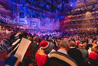 Inside the Royal Albert Hall, full audience singing from carol sheets, illuminated & Christmas trees