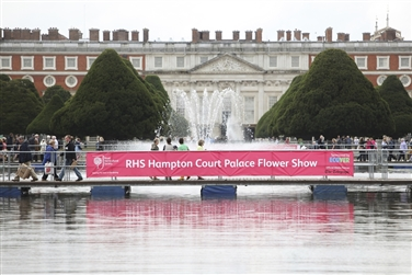 Hampton Court Palace in the background, visitors and a pink RHS banner in the foreground