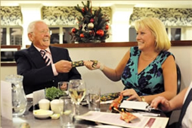 A couple enjoying a meal at a table, pulling a Christmas cracker, with a Christmas tree behind them