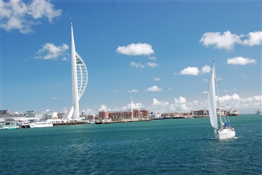 Spinnaker Tower & Gunwharf Quays in the background, a white sailboat in the Solent in the foreground