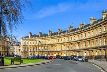The famous 'Crescent' in Bath, curved honey coloured street with a lawn, bench and street light