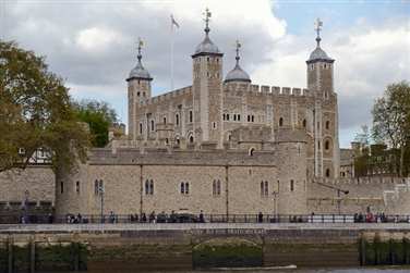 Four large turrets on the main palace with external castle style walls, next to the river Thames
