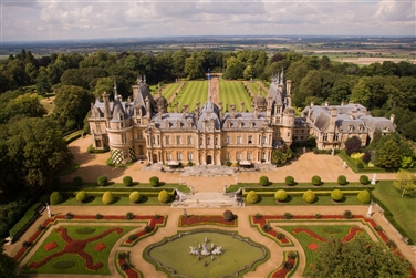 Aerial image of magnificent honey coloured manor house with coloured manicured gardens