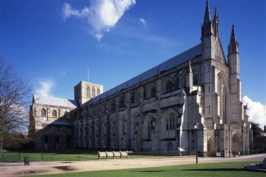Winchester cathedral with a blue sky background, green lawns