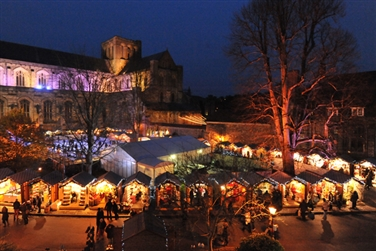 Dark sky, Winchester Cathedral in the background, illuminated Christmas market stalls to the front