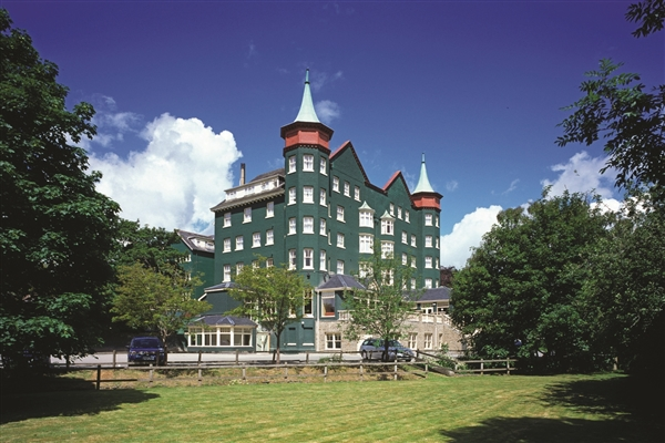 Dark green hotel with turrets located on mowed lawns surrounded by large trees