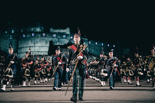 Military persons on parade in tartan in front of Edinburgh Castle at night