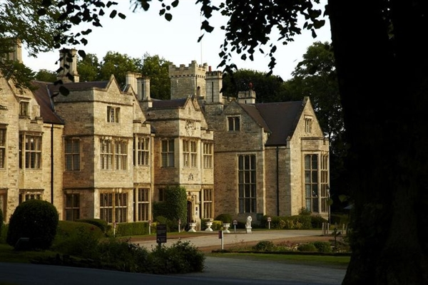Honey coloured stone Jacobean Manor House hotel surrounded by manicured gardens and grounds